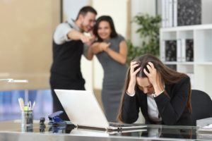 Two businesspeople bullying a sad colleague that is sitting in her workplace at office