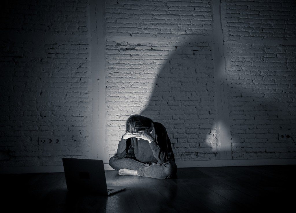 Sad and scared woman with computer laptop