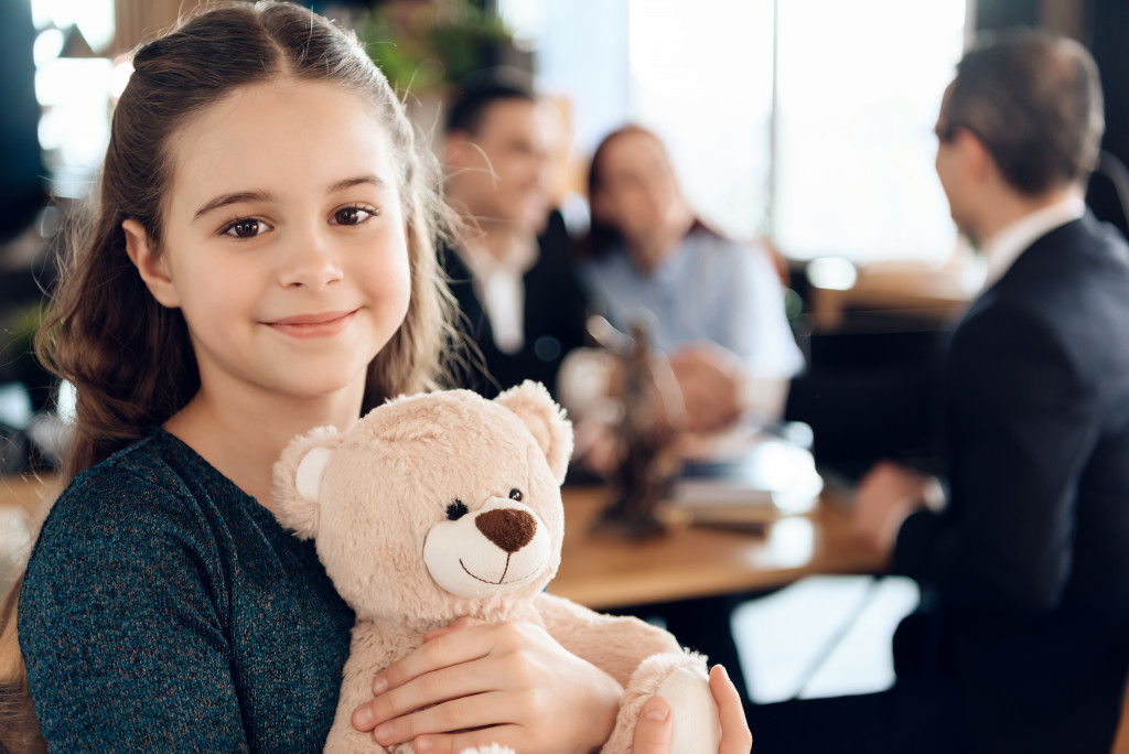 young girl holding stuffed toy